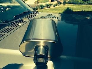 汽车引擎盖顶部的消声器图片。