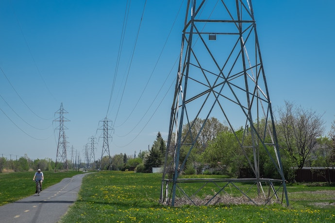 A photograph of transmission lines going down a country road with a bicyclist on the side.