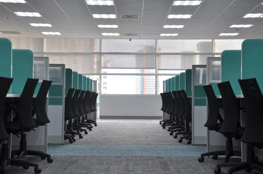一张办公室的照片,里面有两排绿松石色的隔间和空荡荡的黑色办公椅