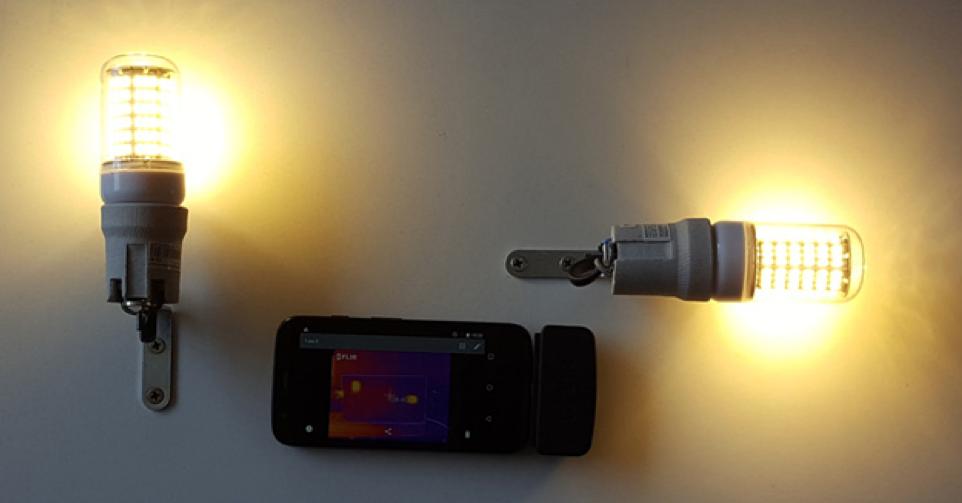用于验证 LED 灯泡模型的实验装置照片,其中打开了两个 LED 灯泡,中间有一个红外摄像头