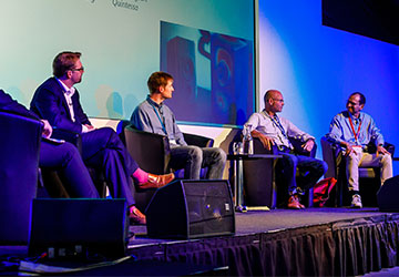 Five speakers sitting spaced apart onstage during a panel discussion; a slide containing an acoustics simulation is visible behind the speakers.