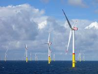 在开阔的海上和多云的天空下,海上风力发电场中的一组涡轮机。