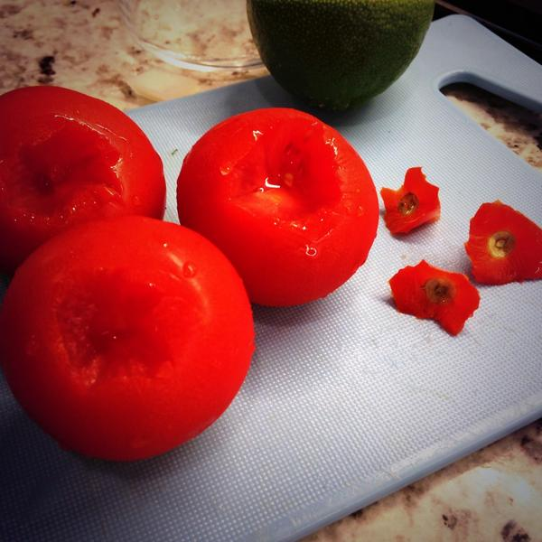 Tomatoes without stems on a cutting board.