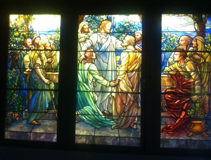 A stained glass window showing a religious scene.