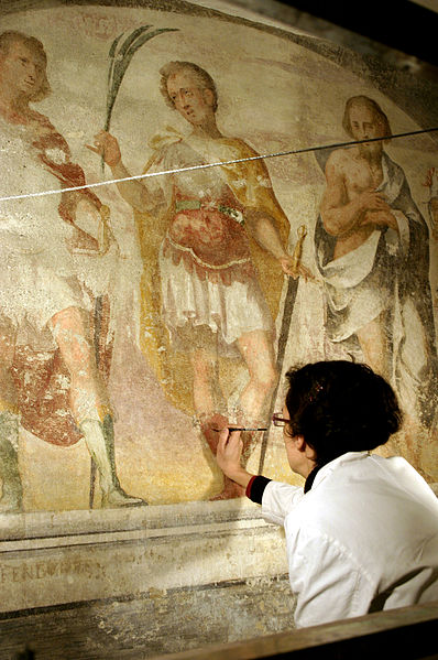An image showing a woman painting damaged frescoes.