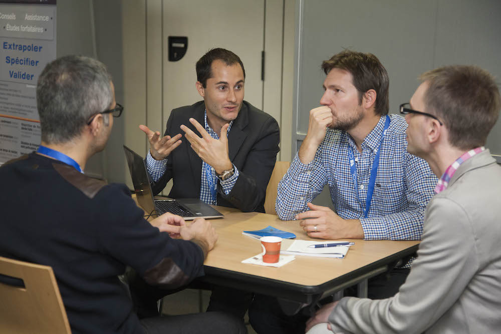 A photo of COMSOL Conference attendees discussing multiphysics simulation.