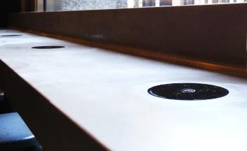 An image showing wireless charging spots on a coffee shop counter.