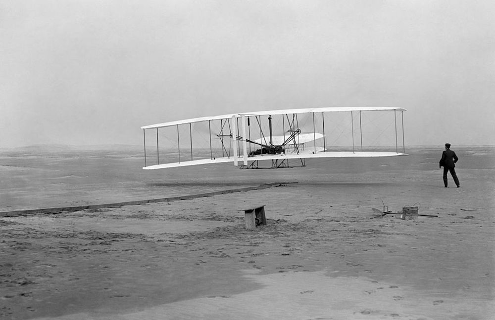 A photograph of the Wright brothers with an early powered airplane.