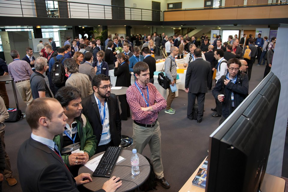 A photograph of conference attendees learning about COMSOL Multiphysics at a demo station.