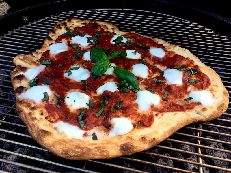 A photo of a pizza on a charcoal grill.
