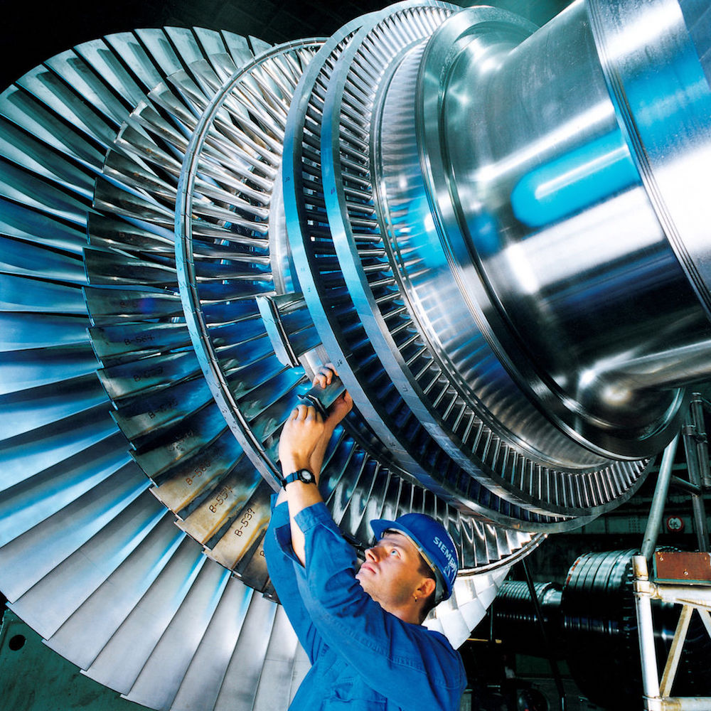 A photo of an engineer working on a steam turbine.