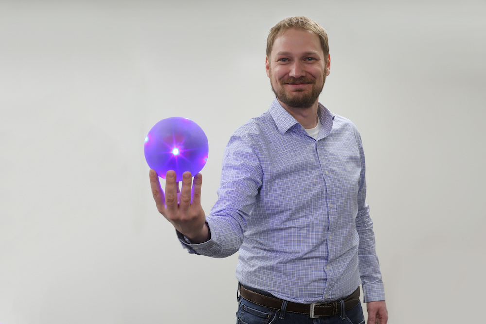 A photograph of a scientist holding an LED sphere in the experimental QSCR room.