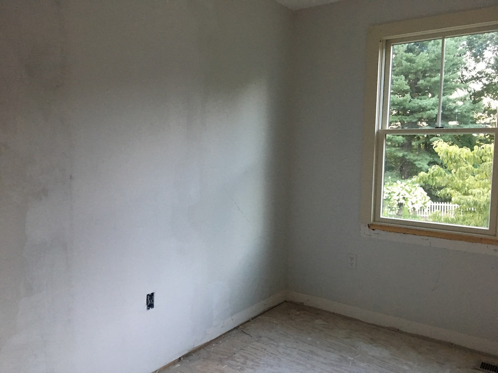 A photo of a bedroom with plastered walls.