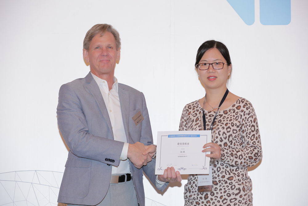 A photograph of Svante Littmarck of COMSOL presenting an award to Xiao Lu.