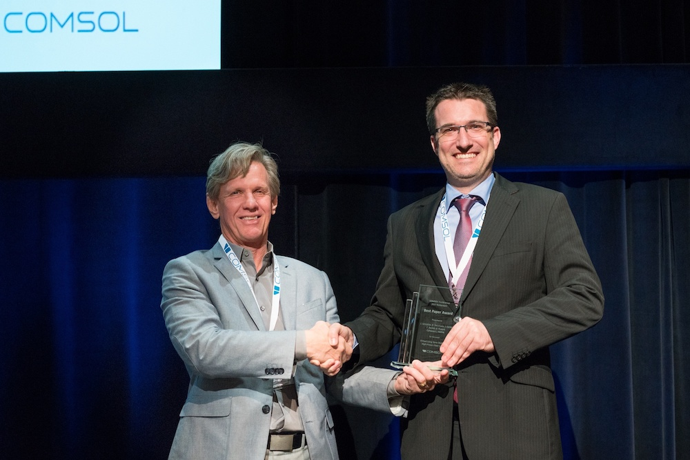 A photograph of J. Schüttler and Svante Littmarck at the conference awards ceremony in Rotterdam.