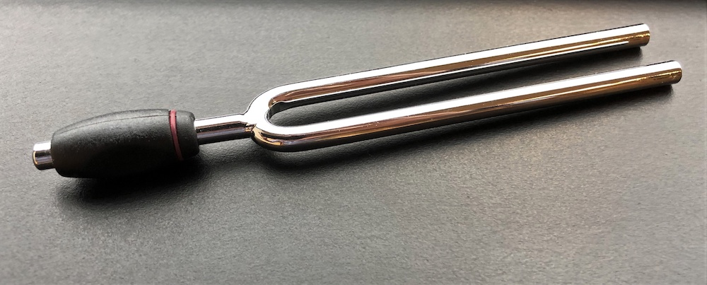 A photo of a tuning fork resting on a table.