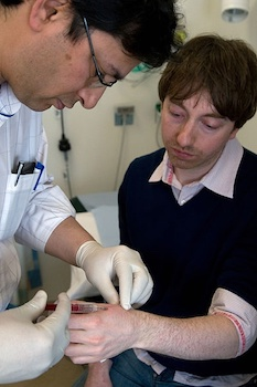 A photo of a surgeon implanting an RFID microchip into someone's hand.