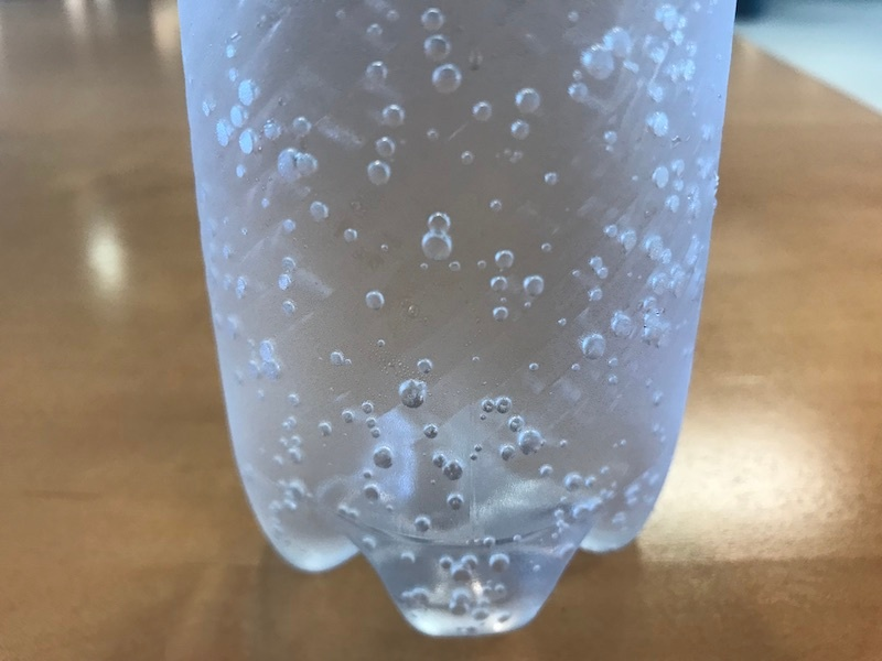 A close-up photo of carbonated water in a bottle.