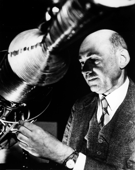 A photograph of Robert Goddard working on a rocket.