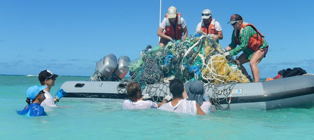 A photograph of divers removing debris from an ocean gyre.