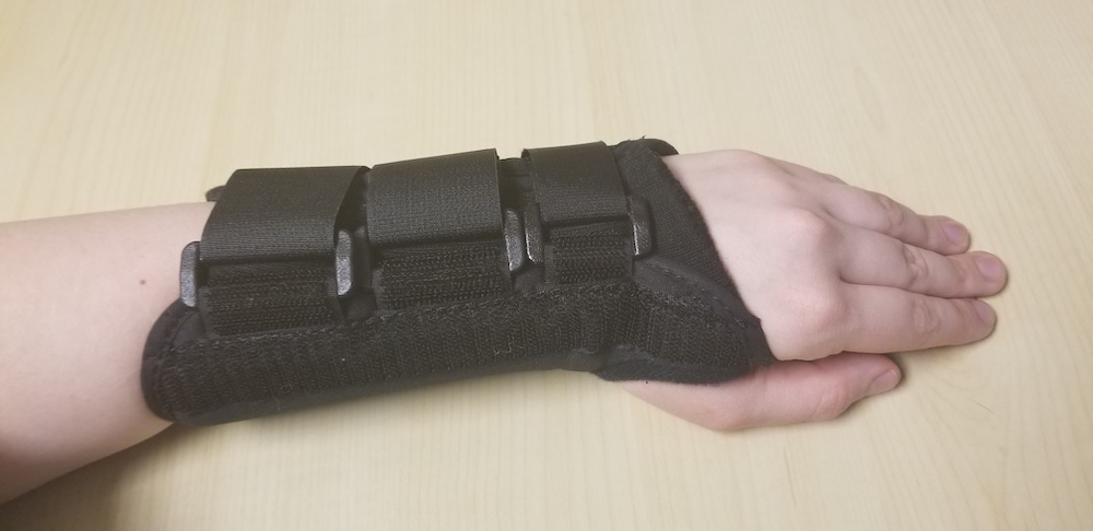 A photograph of a wrist brace worn over an injured forearm.