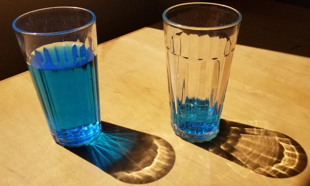 两块玻璃的照片用展示电极平衡概念的能量饮料的不同的水平的。