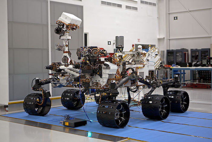 The Curiosity rover standing in a lab.