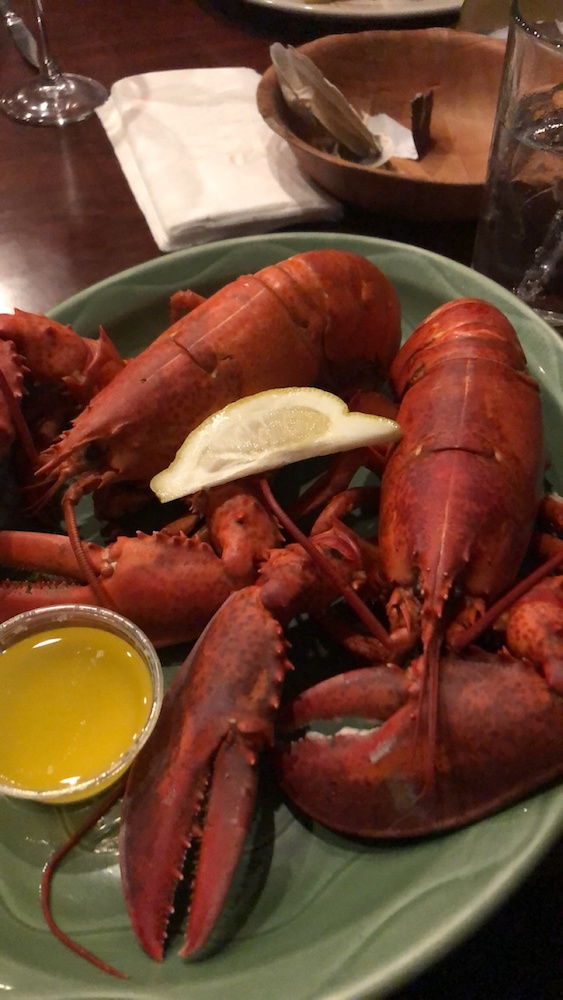 A photograph of two boiled lobsters on a plate.