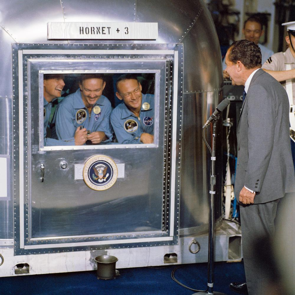 A photograph of the Apollo 11 crew in quarantine and being greeted by Richard Nixon.