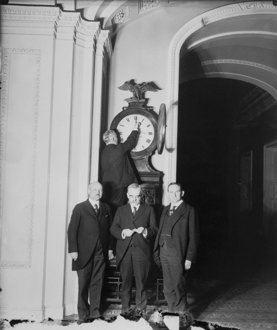A photograph of men setting a clock to the standard time.