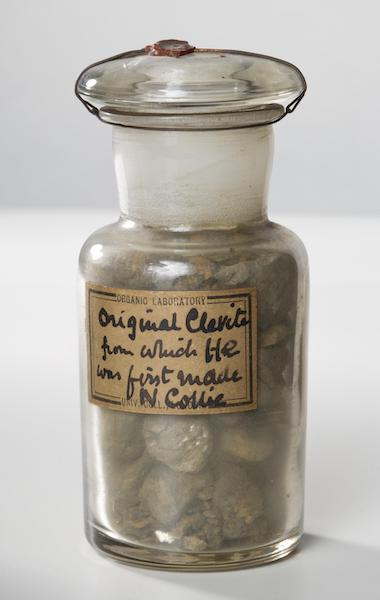 A photograph of a sample of cleveite in a jar.