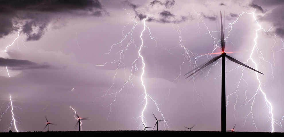 Several wind turbines are struck by lightning against the backdrop of a stormy sky.