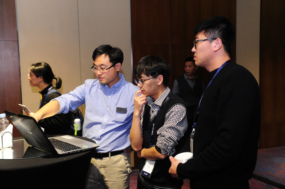 A photograph of attendees discussing modeling problems with a COMSOL application engineer.