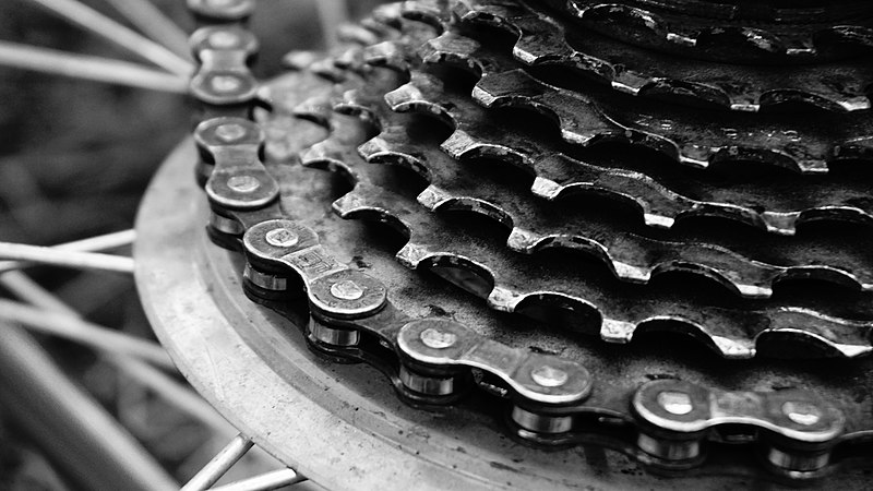 A black-and-white photograph of the chain drive and gears of a bicycle.