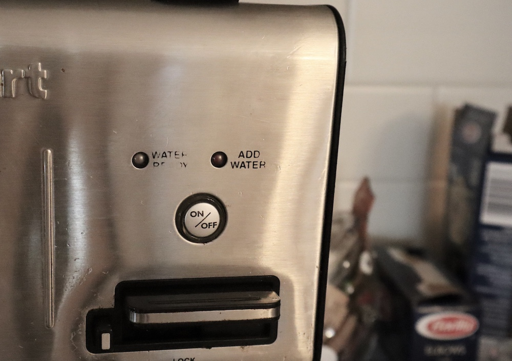 A photo of a coffee maker that looks like a face.