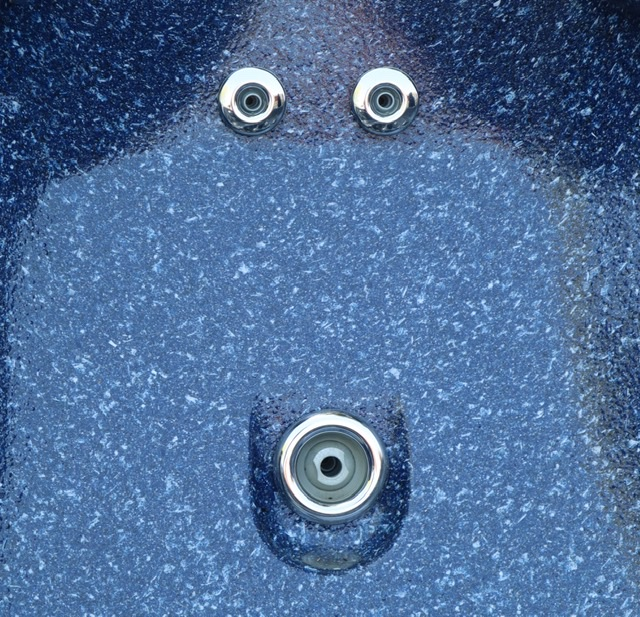 A closeup photograph of hot tub jets forming what looks like a human face, an effect called pareidolia.