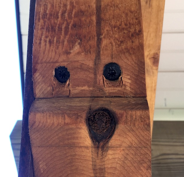 A photograph of a piece of wood with the swirls and knots forming what looks like a face.