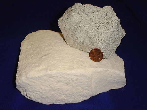 Natural zeolite, which can form molecular sieves, shown in a photograph next to a penny for scale.