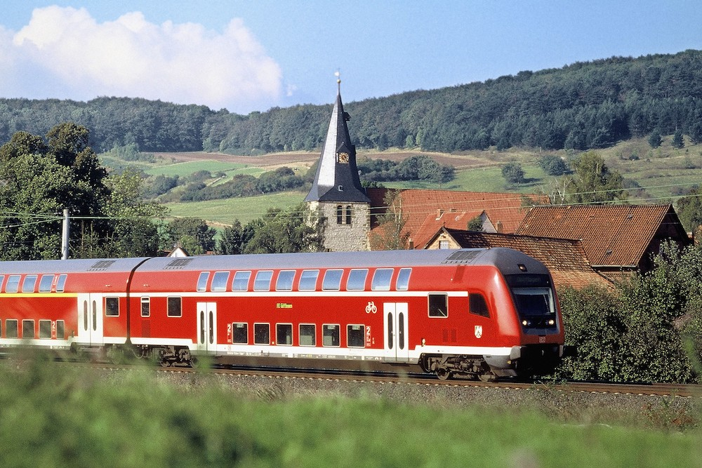 A photograph of a red train riding along a countryside in Germany.