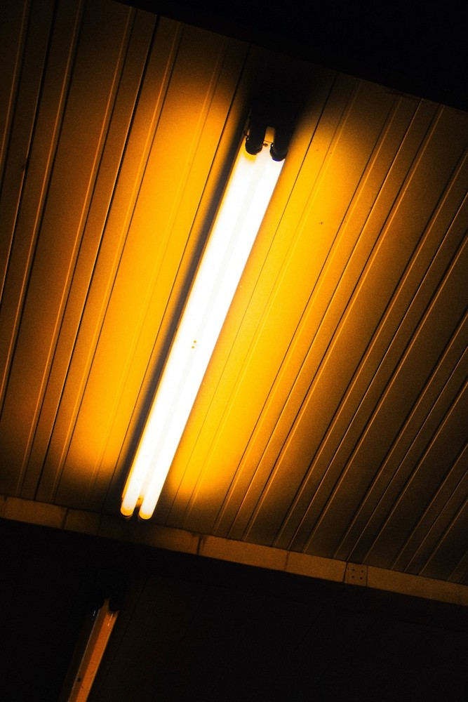 A photograph of a fluorescent bulb on the ceiling of a darkened room.
