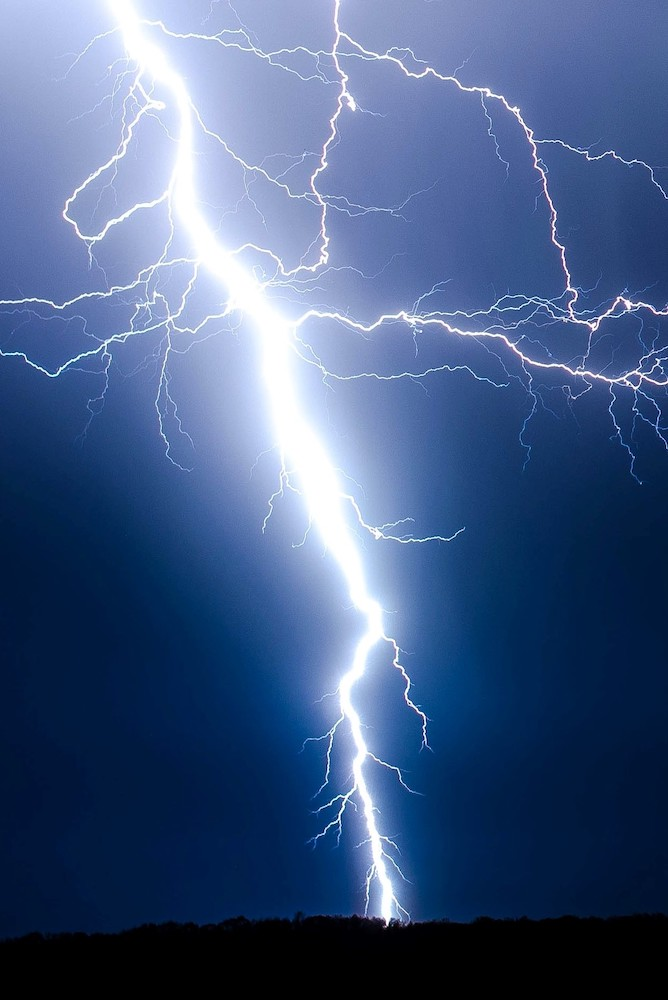 A photograph of a lightning bolt against the backdrop of a dark blue sky.
