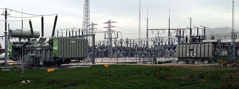 A photograph of an outdoor power station with that includes three-phase transformers.