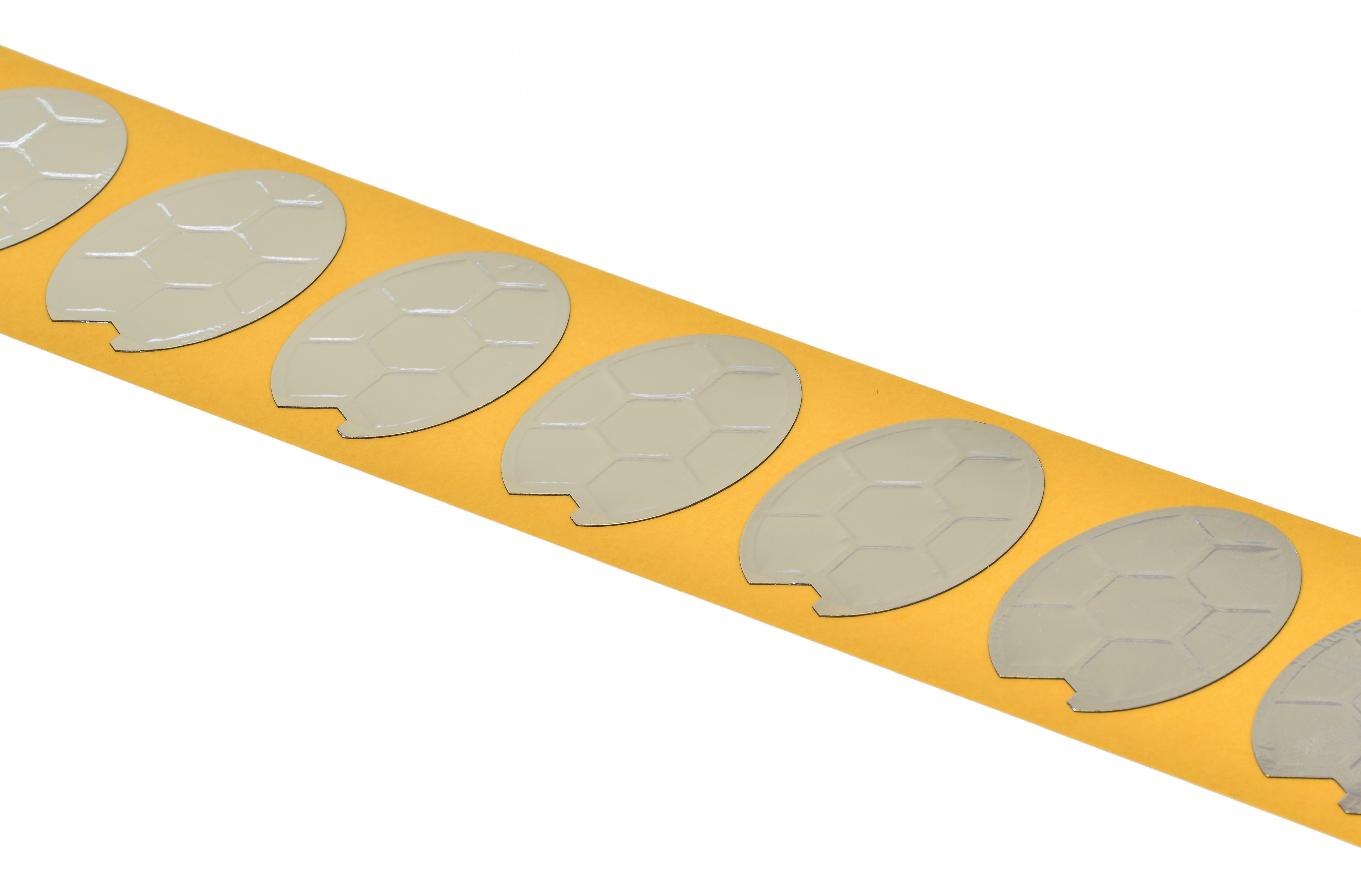 A photograph of an array of high-precision electrostatic laminate transducers on an orange substrate.