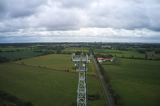 An aerial photograph of a 5G communications tower surrounded by open, green fields.