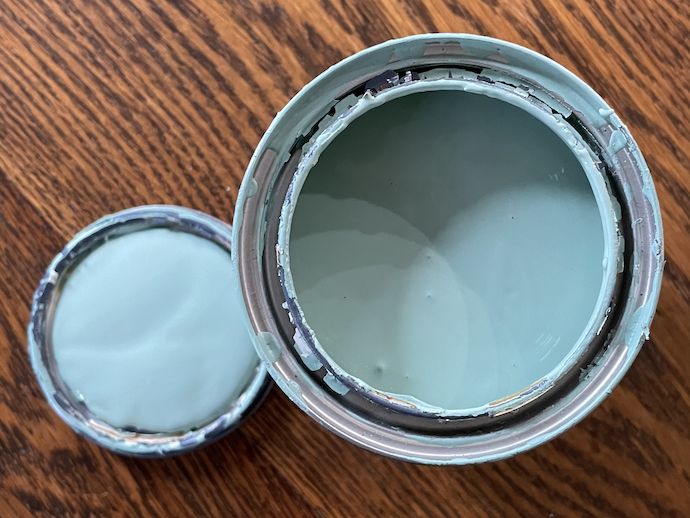 A photograph of a can of blue paint and its lid on a wooden table.