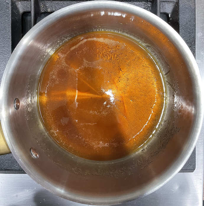 A photograph of a steel pan with some caramelized sucrose at the bottom.