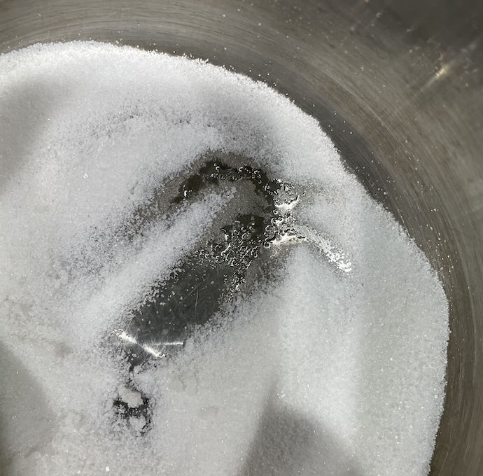 A photograph of the caramel cooking process, zoomed in to show some sugar crystals and water at the bottom of the pan.