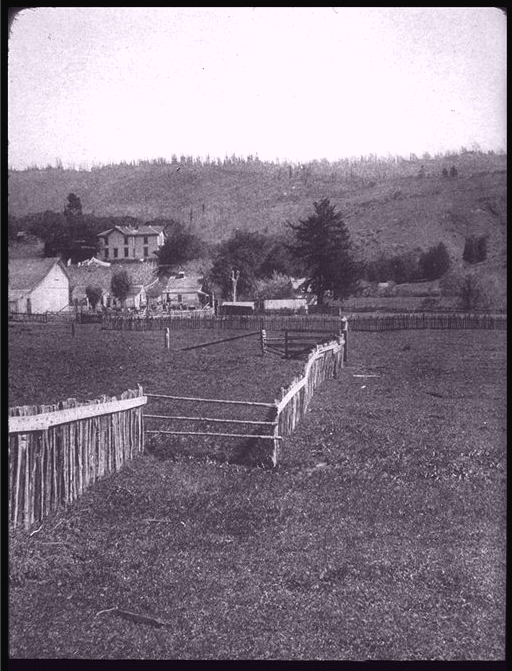 A grayscale photograph from 1906 showing yard that lies over the San Andreas Fault line, with an 8-foot break in a picket fence.
