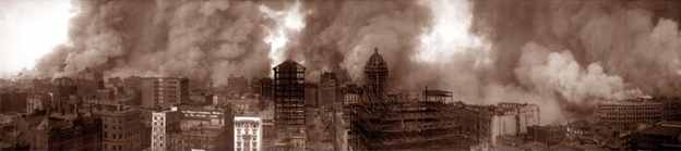A sepia-toned photo of the San Francisco skyline during the 1906 earthquake, with many buildings smoking and on fire.