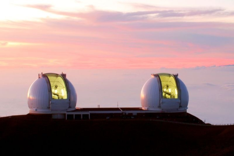 A photograph of the two Keck Telescopes against the backdrop of a pink and purple sunset.